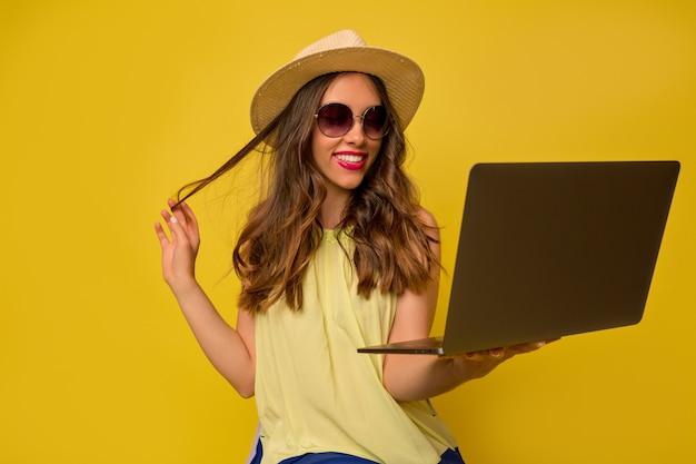 Gelukkig mooie europese vrouw met hoed en zomer bril werken met laptop Gratis Foto