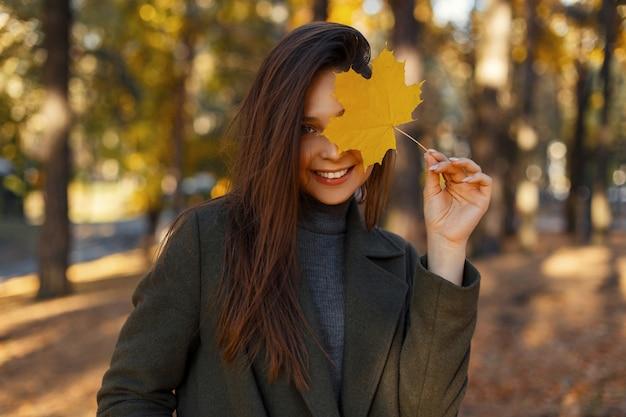 Gelukkig mooie jonge vrouw met een glimlach bedekt haar gezicht met een goudgeel herfstblad en wandelingen in het park Premium Foto