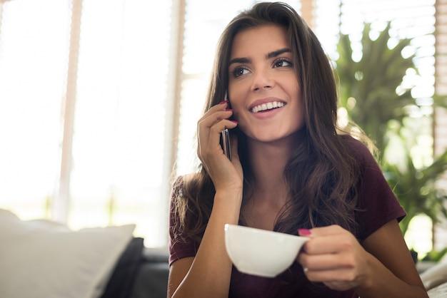 Gelukkig mooie jonge vrouw met koffiekopje en praten via de telefoon Gratis Foto