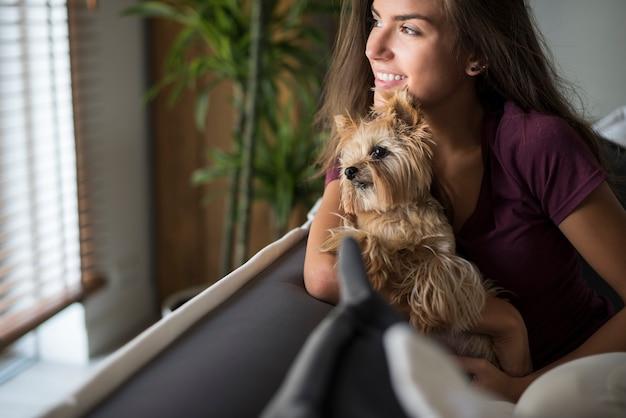 Gelukkig mooie jonge vrouw raam kijken met haar hond Gratis Foto