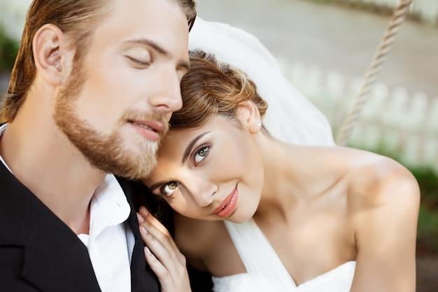 Gelukkig mooie jonggehuwden in pak en trouwjurk glimlachen, genieten. Gratis Foto
