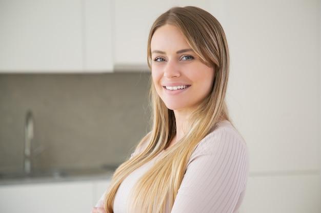 Gelukkig mooie langharige jonge vrouw poseren in de keuken Gratis Foto
