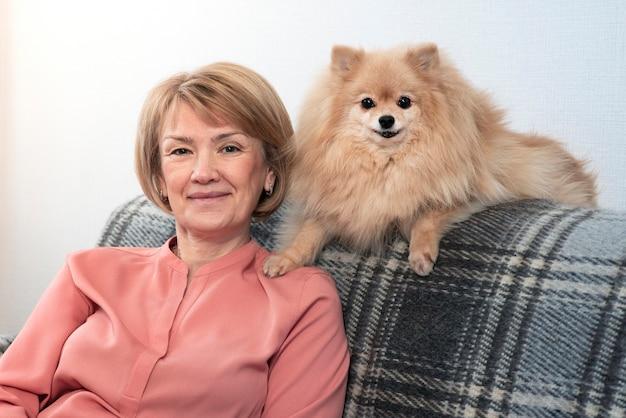 Gelukkig mooie positieve dame, bejaarde senior vrouw zittend op de bank in de huiskamer met haar huisdier, pommeren spitz hond, kleine puppy en lachend. mensen geven om, houden van dieren Premium Foto