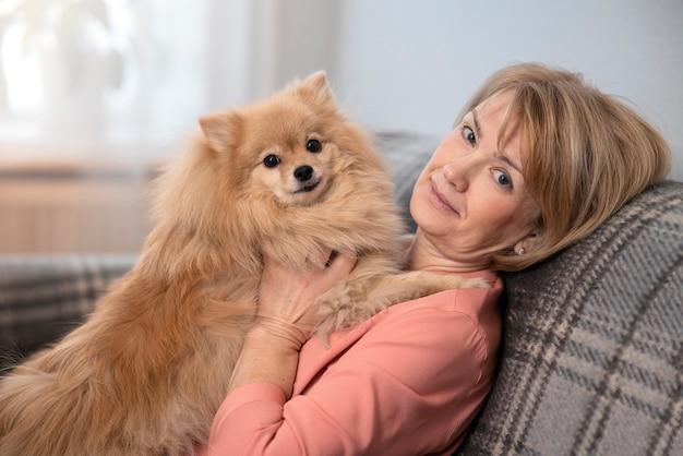 Gelukkig mooie positieve dame, oudere senior vrouw zittend op de bank in de huiskamer met haar Premium Foto