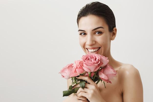 Gelukkig mooie vrouw naakt staan, lachen als boeket rozen ontvangen Gratis Foto