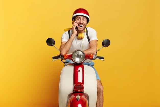Gelukkig motorrijder poseert op snel eigen vervoer, belt klant via smartphone, reist over lange afstand, draagt helm, stereohoofdtelefoon om nek, lacht naar camera. mannelijke bestuurder rijdt scooter Gratis Foto