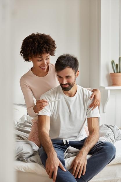 Gelukkig multi-etnisch familiepaar kijkt gelukkig naar zwangerschapstest, voelt zich opgewonden, viert goed nieuws, poseert in de slaapkamer, draagt vrijetijdskleding, zit 's ochtends op een comfortabel bed. vruchtbaarheid concept Gratis Foto