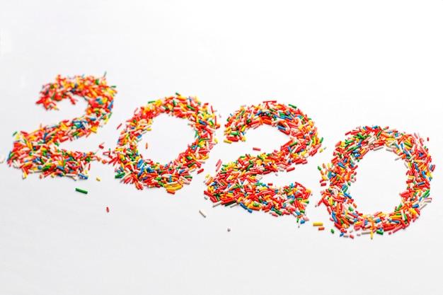 Gelukkig nieuw jaar 2020. de kleurrijke aantalvorm met heldere regenboogsuiker bestrooit geïsoleerd op wit Gratis Foto