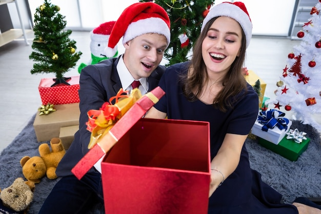 Gelukkig nieuw jaar 2021 concept. gelukkige paar bedrijf uitwisselen van geschenken en een cadeau geven in kerst- en oudejaarsavondfeest Premium Foto