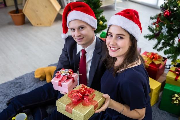 Gelukkig nieuw jaar 2021 concept. gelukkige paar bedrijf uitwisselen van geschenken en een cadeau geven op kerst- en oudejaarsavondfeest kerstboom achtergrond Premium Foto