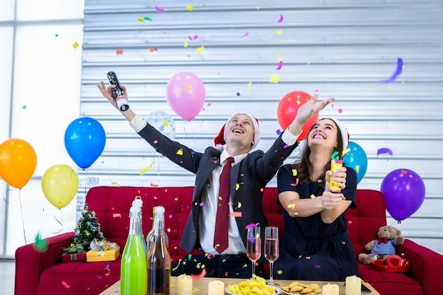Gelukkig nieuw jaar 2021 concept. gelukkige paar papier vuurwerk aansteken met champagne en koekjes op tafel in kerst- en oudejaarsavondfeest Premium Foto