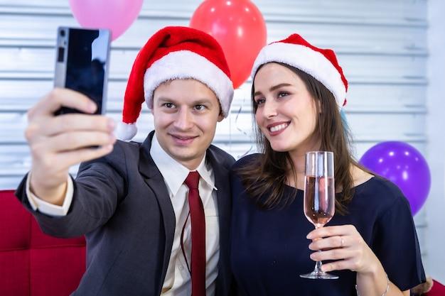Gelukkig nieuw jaar 2021 concept. selfie van het gelukkige paar dat het champagneglas vasthoudt in de kerst- en oudejaarsavond Premium Foto