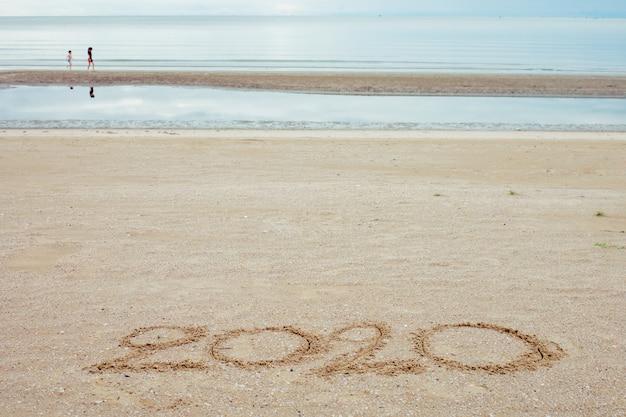 Gelukkig nieuwjaar 2020, belettering op het strand met golf en heldere blauwe zee. Premium Foto