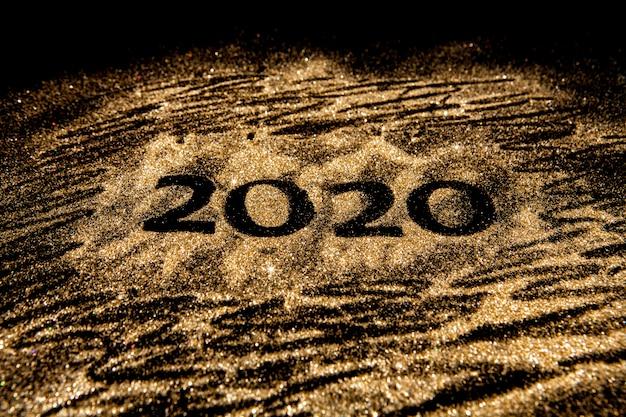 Gelukkig nieuwjaar 2020. creatieve collage van nummer twee en nul is het jaar 2020. mooi sprankelend gouden nummer 2020 op zwart. Premium Foto