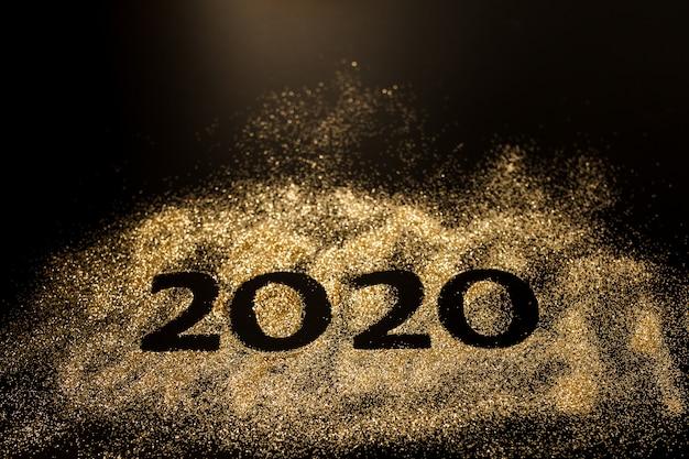 Gelukkig nieuwjaar 2020. creatieve collage van nummer twee en nul uit het jaar 2020. mooi sprankelend gouden nummer 2020 op zwart Premium Foto