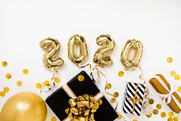 Gelukkig nieuwjaar 2020 viering. goudfolie ballonnen cijfer 2020 op witte achtergrond met geschenken Premium Foto