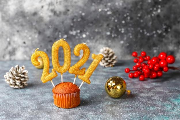 Gelukkig nieuwjaar 2021, cupcakes met gouden kaarsen. Gratis Foto