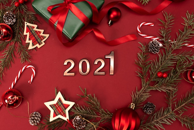 Gelukkig nieuwjaar 2021. gouden cijfers 2021 met kerst hoed zijn op rode achtergrond met glitter. holiday party decoration of briefkaart concept met bovenaanzicht en kopie ruimte. Premium Foto