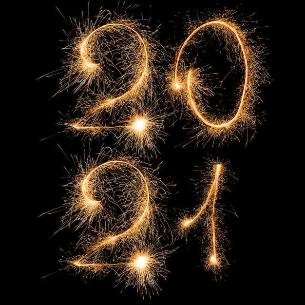 Gelukkig nieuwjaar 2021. nummer 2021 geschreven sprankelende wonderkaarsen in twee regels geïsoleerd op zwarte achtergrond met kopie ruimte voor tekst. Premium Foto