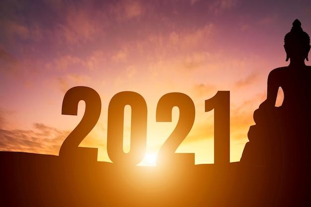 Gelukkig nieuwjaar 2021. silhouet boeddhabeeld vroege ochtend zonsopgang boven de horizon achtergrond Premium Foto