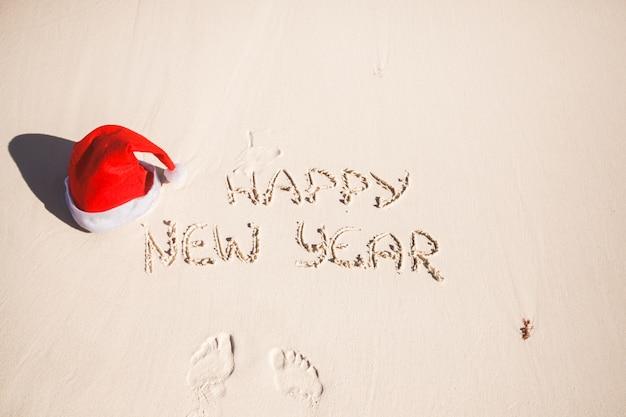 Gelukkig nieuwjaar geschreven in het zand en de kerstmuts op wit zandstrand Premium Foto