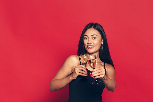 Gelukkig nieuwjaar voor jou. een jonge en mooie vrouw dansen met glas champagne Premium Foto