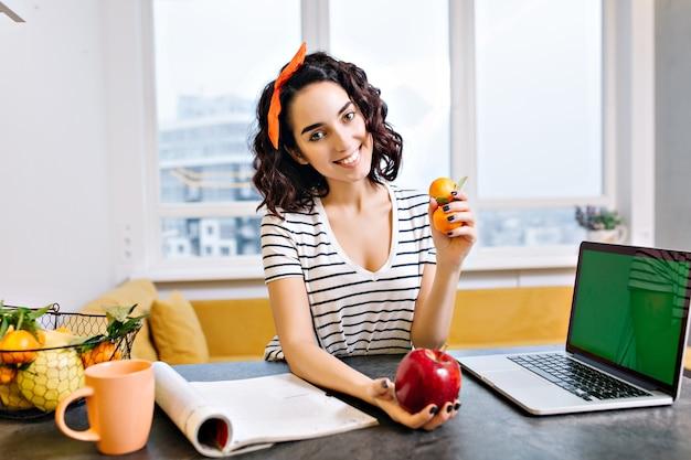 Gelukkig ontspannen tijd thuis van vrolijke jonge vrouw met geknipte krullend haar lachend op tafel in de woonkamer. laptop met groen scherm, citrus, appel, tijdschrift, thee, chillen in modern appartement Gratis Foto