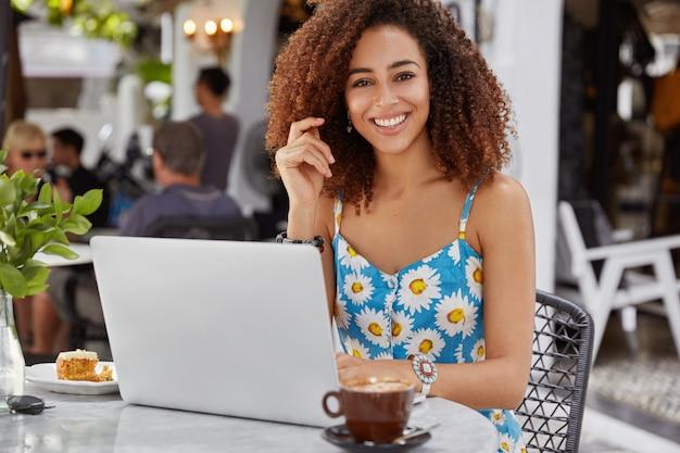 Gelukkig opgetogen vrouwelijke freelancer met krullend haar en donkere huid, draagt blauwe bloem bedrukte blouse, werkt op draagbare laptopcomputer Gratis Foto
