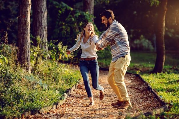 Gelukkig opgewekt kaukasisch jong paar dat op sleep in hout loopt en goede tijd heeft. man die de hand van de vrouw houdt. avontuur in de natuur concept. Premium Foto