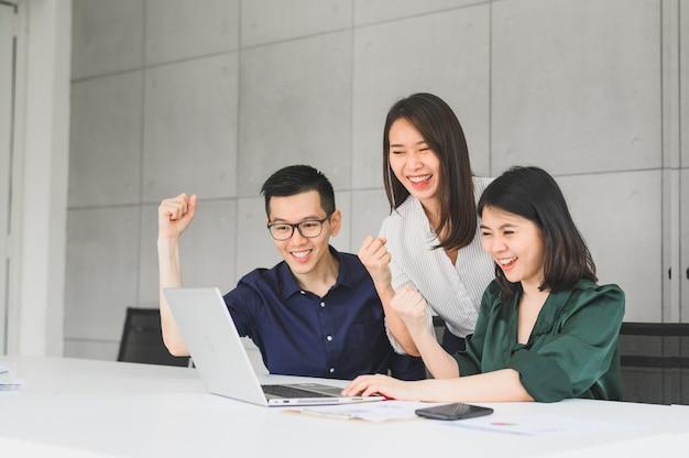 Gelukkig opgewonden aziatisch commercieel team dat wapen opheft om succes te vieren Premium Foto