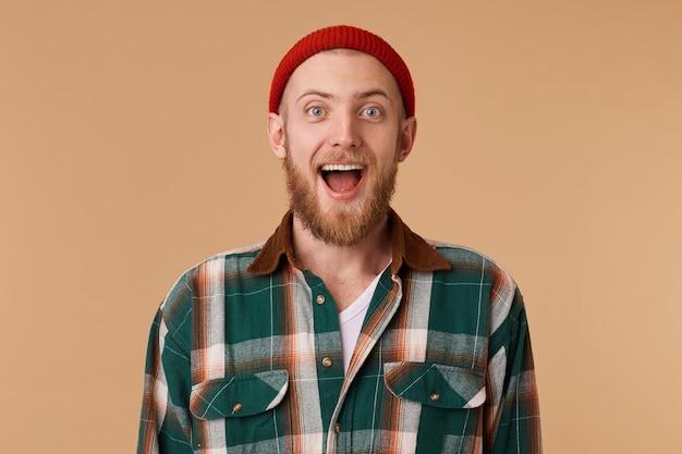 Gelukkig opgewonden bebaarde man in rode hoed geïsoleerd over beige muur Gratis Foto
