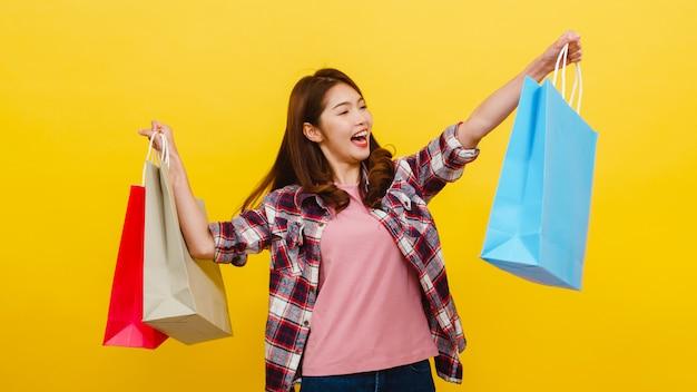 Gelukkig opgewonden jonge aziatische dame met boodschappentassen met hand verhogen in casual kleding en camera kijken op gele muur. gelaatsuitdrukking, seizoensgebonden verkoop en consumentisme concept. Gratis Foto