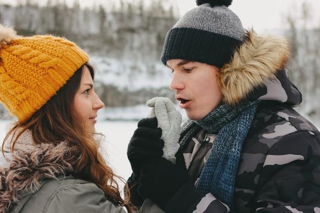 Gelukkig paar bij bosaardpark in koud seizoen. de man verwarmt de handen van het meisje Premium Foto