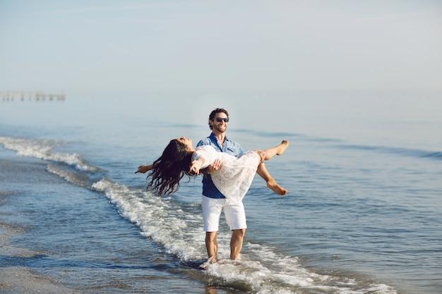 Gelukkig paar dat en op het strand loopt speelt Premium Foto