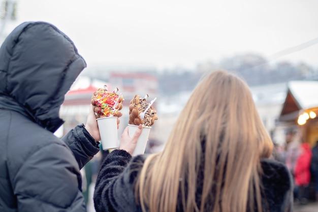 Gelukkig paar dat in warme kleren in liefde bellenwafels eet bij kerstmismarkt. vakanties, winter, kerstmis en mensen Premium Foto