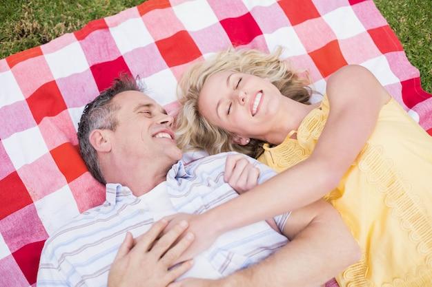 Gelukkig paar dat op een deken op het gras koestert Premium Foto