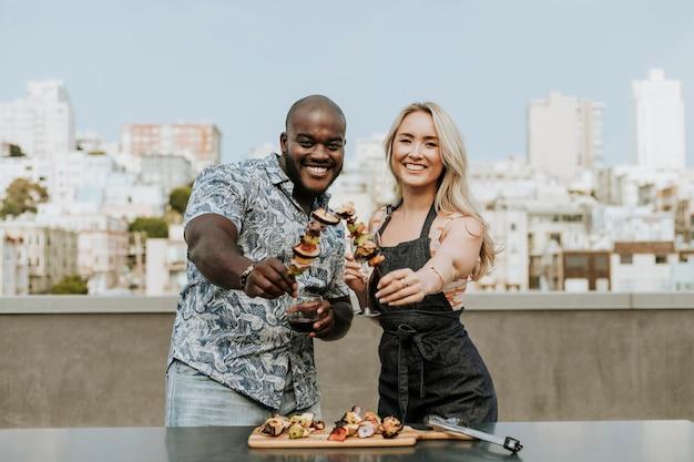 Gelukkig paar dat van een barbecuevleespen en een glas wijn geniet Premium Foto