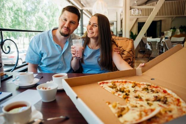 Gelukkig paar dat van pizza en milkshake in koffie geniet Gratis Foto