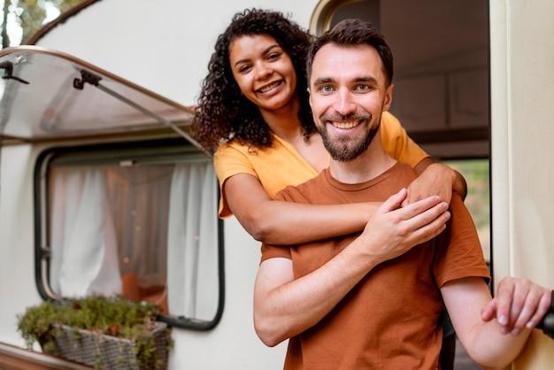 Gelukkig paar dat zich voor kampeerauto bevindt Gratis Foto