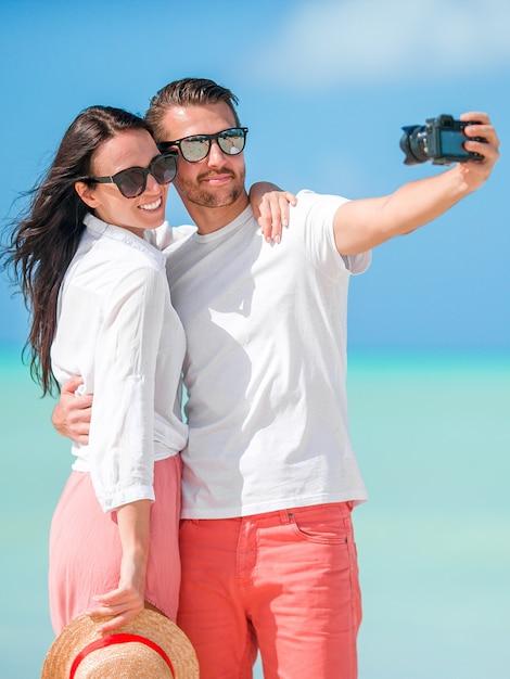 Gelukkig paar die een selfiefoto op wit strand nemen. twee volwassenen die van hun vakantie op tropisch exotisch strand genieten Premium Foto