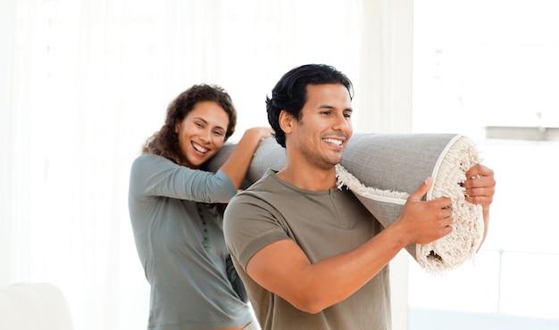 Gelukkig paar die een tapijt samen in hun nieuwe woonkamer houden Premium Foto
