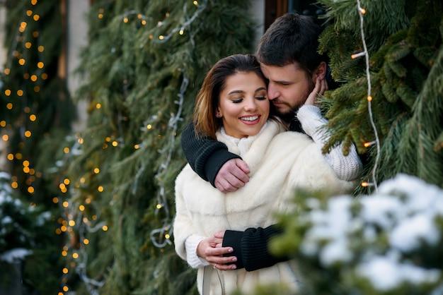 Gelukkig paar die in warme kleren elkaar op kerstmisboom koesteren met lichten. wintervakantie, kerstmis en nieuwjaar. Premium Foto
