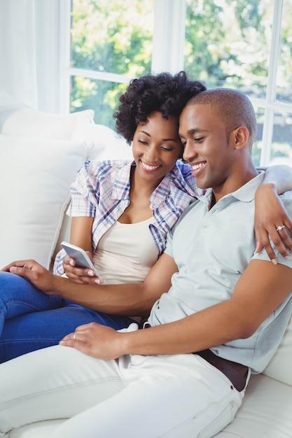 Gelukkig paar die smartphone op de bank in de woonkamer gebruiken Premium Foto