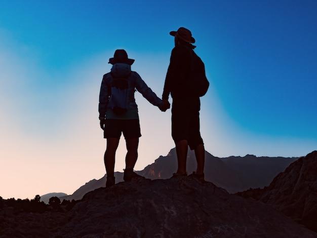 Gelukkig paar die zich op de piek van berg verenigen en bij adembenemend uitzicht bij zonsondergang letten op Premium Foto