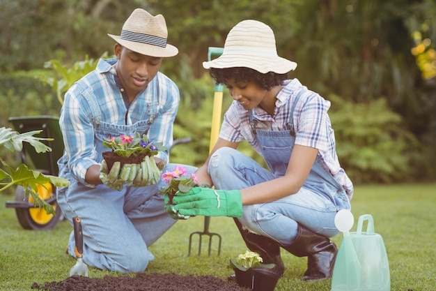 Gelukkig paar in de bloemen van de tuinholding Premium Foto