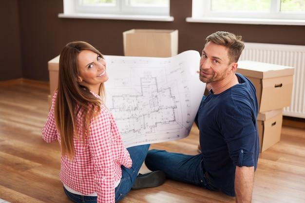 Gelukkig paar in nieuw appartement met blauwdruk Gratis Foto