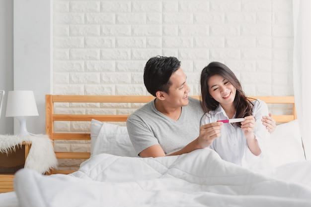 Gelukkig paar met zwangerschapstest in slaapkamer Premium Foto