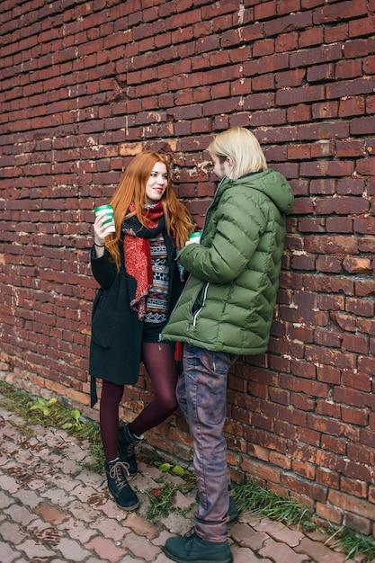 Gelukkig paar toeristen in warme stedelijke kleren die zich met koffie beschikbare koppen bevinden op bakstenen muur Premium Foto