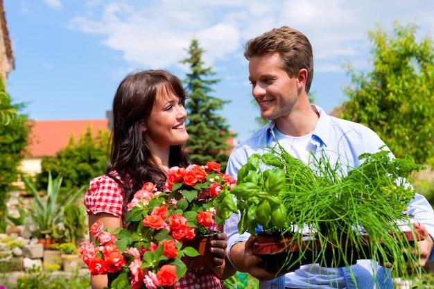 Gelukkig paar trots met hun ingemaakte kruiden en bloemen Premium Foto