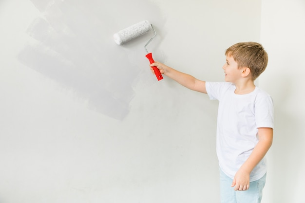 Gelukkig peuter kind schilderij muur. reparatie in appartement. het concept van verhuizen naar een nieuw appartement. schattige kleine jongen schilderij muur in de kamer Premium Foto